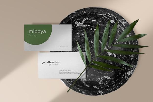 Sauberes minimales visitenkartenmodell auf schwarzer marmorplatte