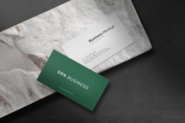 Sauberes minimales visitenkartenmodell auf steinplatte mit schattenhintergrund.