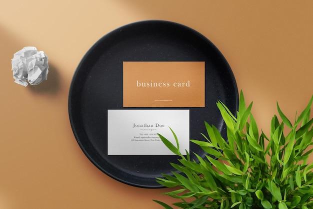 Sauberes minimales visitenkartenmodell auf weißem stoff und tonplatte