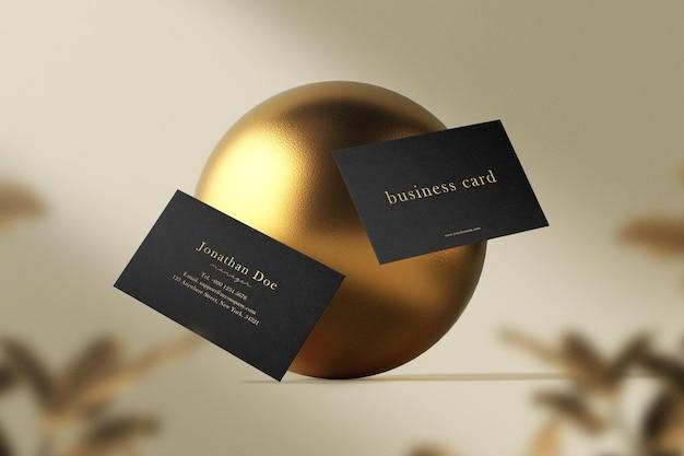 Sauberes minimales visitenkartenmodell, das auf goldkugel mit blättern schwimmt