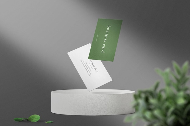 Sauberes minimales visitenkartenmodell, das auf weißer kreisbasis mit blättern schwimmt