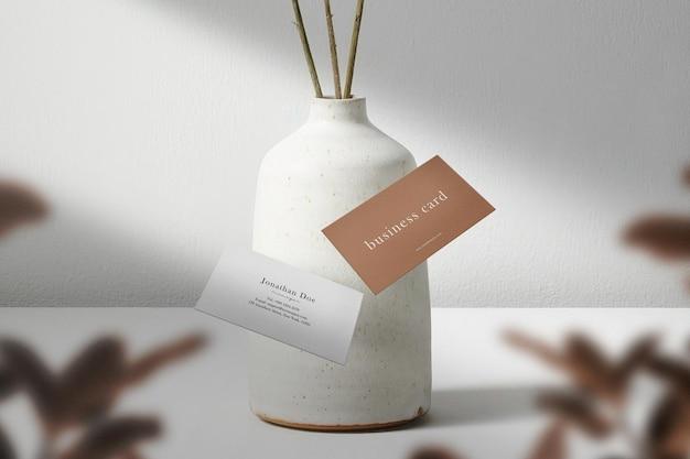 Sauberes minimales visitenkartenmodell, das auf weißer vase schwimmt