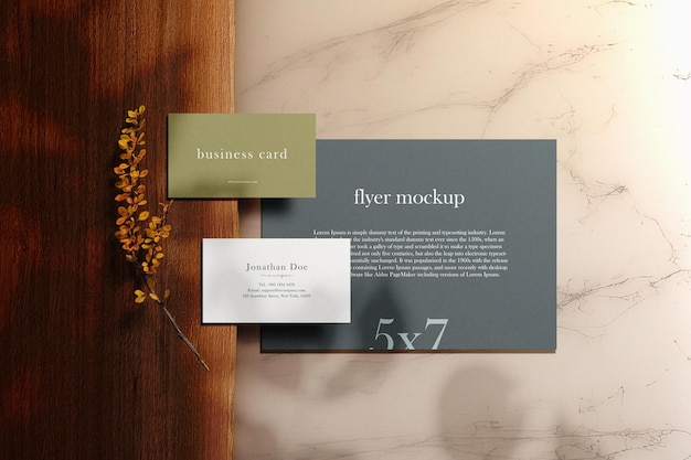 Sauberes minimalistisches visitenkarten- und flyermodell auf holzplatte mit marmor und blättern