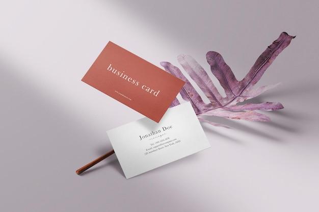 Sauberes minimalistisches visitenkartenmodell, das auf blättern schwimmt