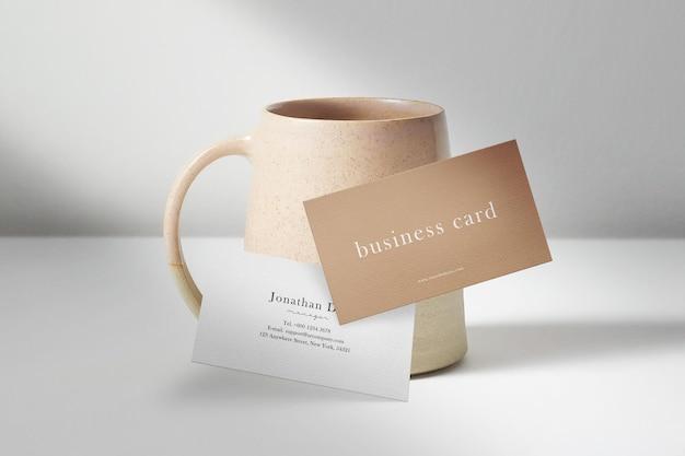 Sauberes minimalistisches visitenkartenmodell, das vor einer teetasse schwebt