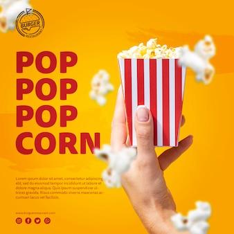 Schablonenhand, die popcorntasche hält
