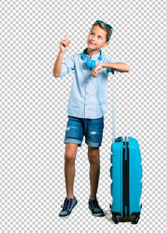 Scherzen sie mit der sonnenbrille und den kopfhörern, die mit seinem koffer reisen, der mit der indexflosse zeigt