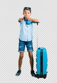 Scherzen sie mit der sonnenbrille und kopfhörern, die mit seinem kofferzeigen reisen