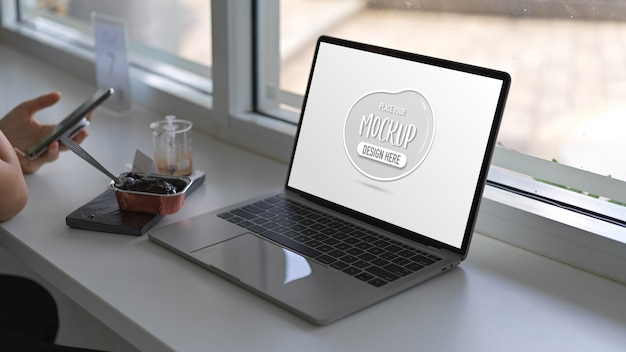Schließen sie herauf ansicht der frau, die smartphone mit modell-laptop-computer auf weißem tisch hält