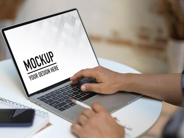 Schließen sie herauf ansicht der männlichen hände, die mit laptop-modell arbeiten