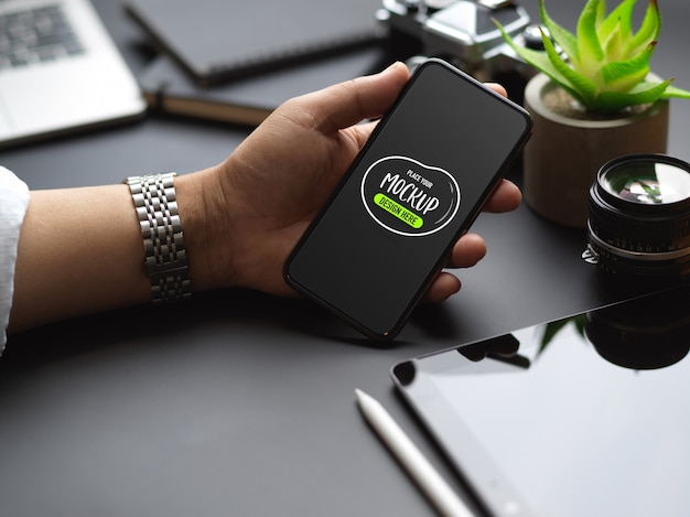 Schließen sie herauf ansicht der männlichen hand, die verspottetes smartphone auf schwarzem arbeitstisch mit büromaterial hält