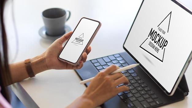 Schließen sie herauf ansicht der weiblichen hand, die mit digitalem tablett und smartphone-modellbildschirm arbeitet