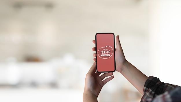 Schließen sie herauf ansicht der weiblichen hand, die verspottetes smartphone hält