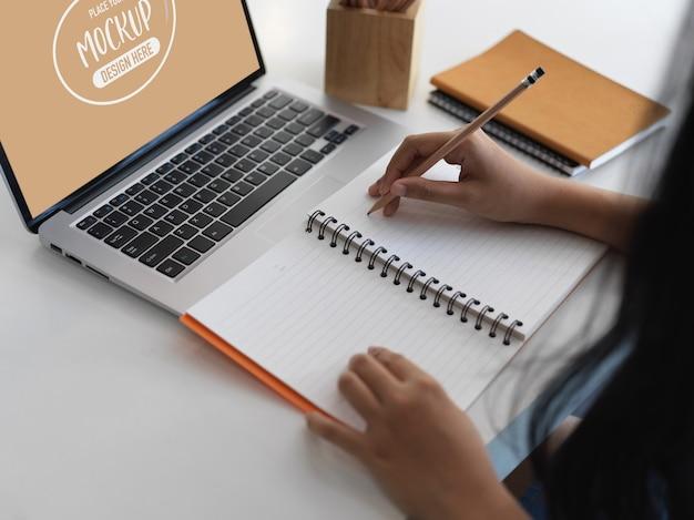 Schließen sie herauf ansicht des büroangestellten, der auf notizbuch schreibt, während sie bildschirm-laptop-modell verwenden