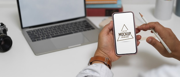 Schließen sie herauf ansicht des männlichen unternehmers, der modell smartphone während der arbeit mit laptop auf arbeitstisch verwendet