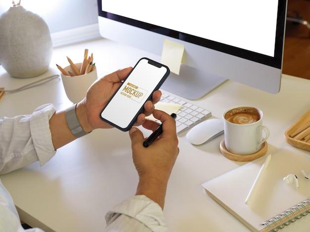 Schließen sie herauf des geschäftsmannes, der smartphone mit modellbildschirm in seinen händen verwendet