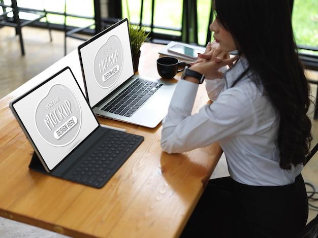 Schließen sie oben auf arbeiterin mit modell laptop und tablet