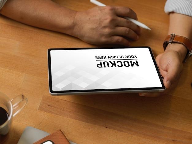 Schließen sie oben vom geschäftsmann unter verwendung des digitalen tablettenmodells auf holztisch