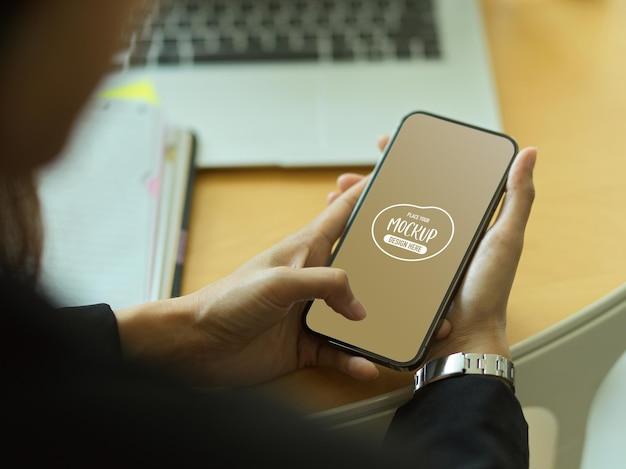 Schließen sie oben von den händen des unternehmers unter verwendung des smartphones mit modellbildschirm
