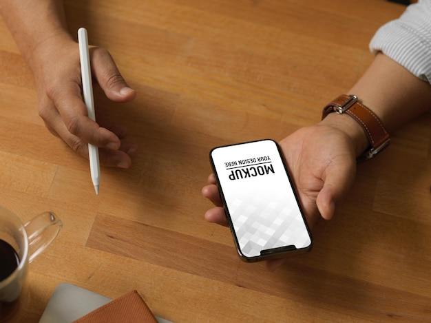 Schließen sie oben von geschäftsmannhand, die smartphone-modell auf holztisch hält