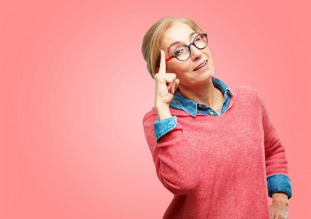 Schöne ältere frau, die glücklich und überrascht schaut, an einer fantastischen neuen idee lächelt und denkt