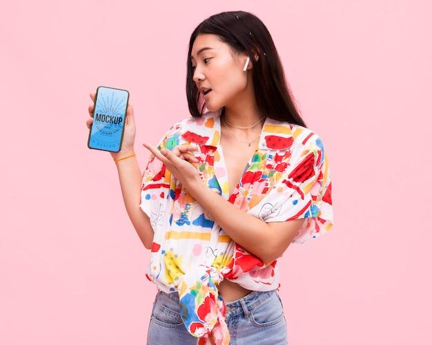 Schöne frau mit smartphone-modell