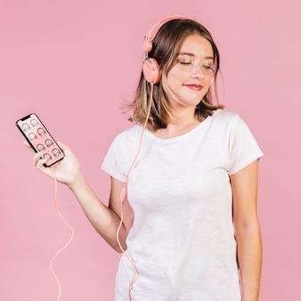 Schöne junge frau mit kopfhörern und einem mobiltelefonmodell