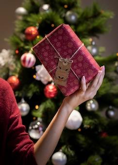 Schönes eingewickeltes geschenk mit dem aufkleber und seil in der hand gehalten