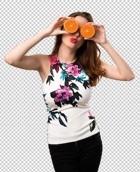 Schönes junges mädchen, das orange scheiben als gläser trägt