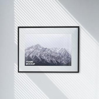 Schönes sauberes modell des foto-bild-plakats im schwarzen horizontalen rahmen auf der wand