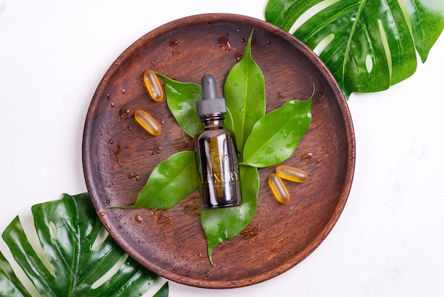 Schönheitsprodukte mit omega-3-gelkapseln und serum in glasflaschen, grüne blätter auf holzteller auf weißem hintergrund.
