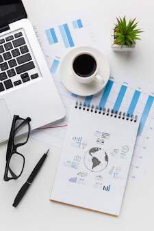 Schreibtisch mit kaffee, laptop und notebook-modell