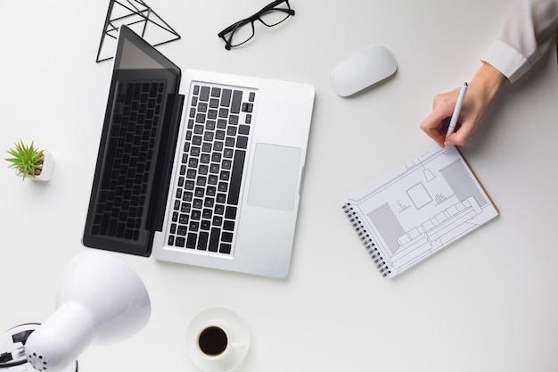 Schreibtisch mit laptop und mann, der auf notizbuchmodell schreibt