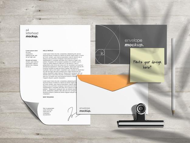 Schreibwaren-markenidentitätsmodellvorlage und szenenersteller mit briefkopf, umschlägen und haftnotiz auf holztisch