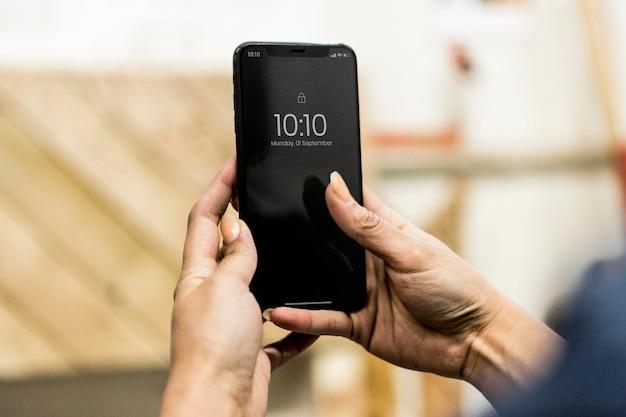 Schreinerin mit ihrem telefon in einer werkstatt