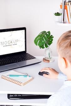 Schuljunge, der zu hause laptop auf einer tabelle verwendet