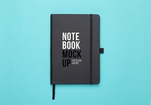 Schwarze notizbuchmodellvorlage für ihr design auf blau