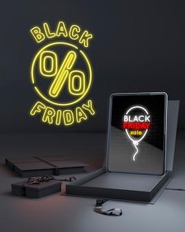Schwarzer freitag-hintergrund mit tablette und gelben neonlichtern
