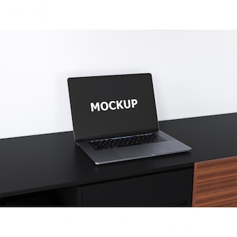 Schwarzer laptop mockup auf einem schreibtisch