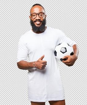 Schwarzer mann, der eine fußballkugel anhält