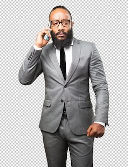 Schwarzer mann des geschäfts, der auf einem mobile spricht
