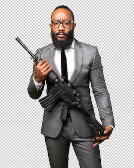 Schwarzer mann des geschäfts, der ein maschinengewehr hält