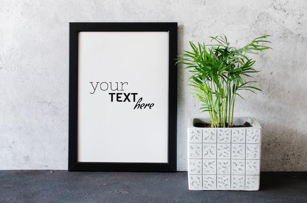 Schwarzer plakat- oder fotorahmen und schöne pflanze im betontopf. zimmer im skandinavischen stil.
