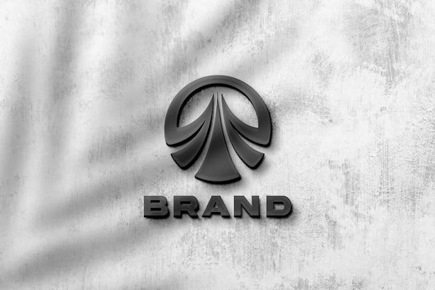 Schwarzes logomodell auf grauer wand