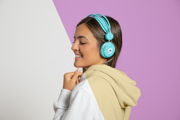 Seitenansicht der frau, die musik auf kopfhörern hört