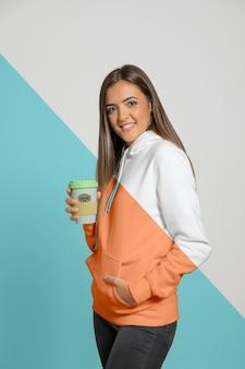 Seitenansicht der frau im hoodie, der kaffeetasse hält
