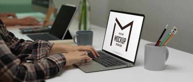 Seitenansicht der weiblichen büroangestellten, die auf modell-laptop-tastatur auf arbeitstisch im büroraum tippt