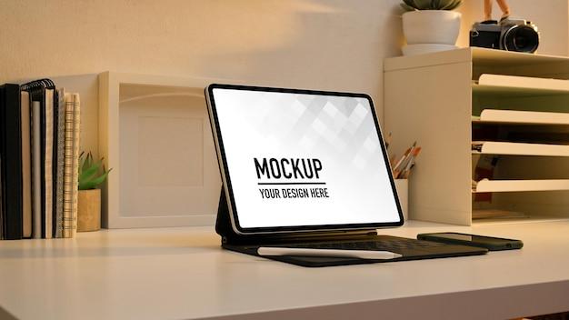 Seitenansicht des arbeitstisches mit digitalem tablet-modell und zubehör im home-office-raum