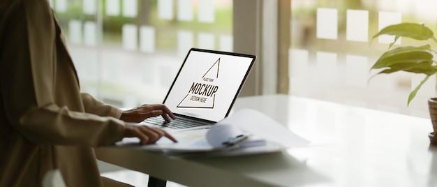 Seitenansicht des weiblichen büroangestellten, der mit modell-laptop arbeitet