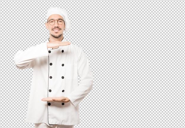 Selbstbewusster junger koch, der eine geste macht, etwas mit seinen händen zu halten